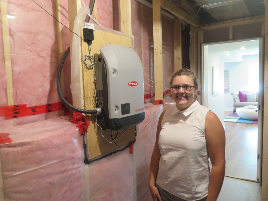 Rebecca Hagen displays the solar photovoltaic inverter in Ottawa.